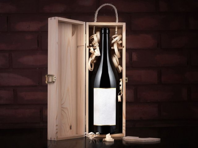 Bottle of wine in a wooden case against a brick wall background. Presentation of wine in the warehouse.