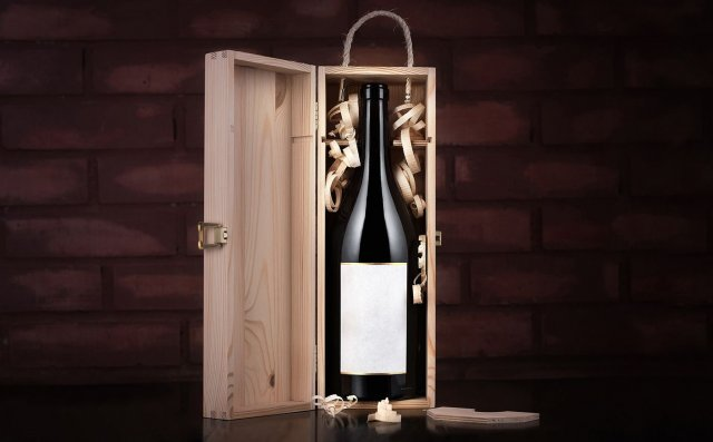 Bottle of wine in a wooden box against a brick wall background.